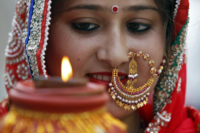 A woman prays during the Hindu festival of Karva Chauth inside a temple in Chandigarh October 11, 2014. (Photo by Ajay Verma/Reuters)