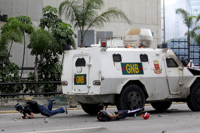 """Demonstrators fall on the ground after being hit by a riot police armoured vehicle while clashing with the riot police during a rally against Venezuelan President Nicolas Maduro in Caracas, Venezuela, May 3, 2017. Marco Bello: """"In that moment, demonstrators attacked a couple of National Guards when they fell off a bike during clashes. Then another National Guard driving an armoured vehicle ran over the motorbike, trying to intimidate demonstrators and to rescue their fellow guards. The reaction of the crowd was to attack, throwing rocks and molotov cocktails and trying to jump over the truck. In the midst of confrontation and confusion, the driver drove back hitting people"""". (Photo by Marco Bello/Reuters)"""
