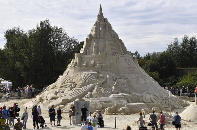 People watching a giant sandcastle in Duisburg, Germany, Friday, September 2, 2016. The castle  was made of 2300 tons of sand. (Photo by Martin Meissner/AP Photo)