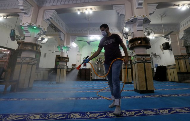 A volunteer wearing a face mask sprays disinfectant inside a mosque as it is prepared for prayer after being reopened, following the outbreak of the coronavirus disease (COVID-19), in Cairo, Egypt, June 26, 2020. (Photo by Mohamed Abd El Ghany/Reuters)