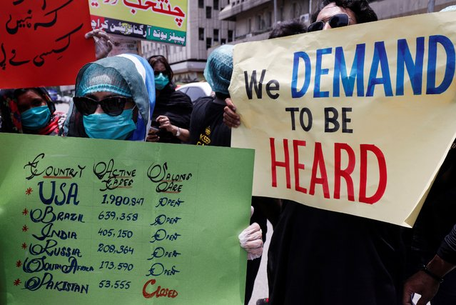 Salon workers hold signs during a protest demanding to reopen of their business, after provincial government extended the ban on beauty parlors as a precautionary measures to stem the coronavirus disease (COVID-10) in Karachi, Pakistan on July 22, 2020. (Photo by Akhtar Soomro/Reuters)