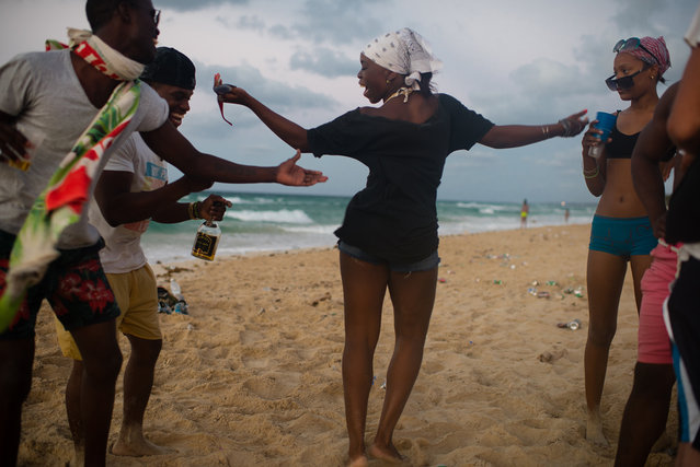 Yanelis Blanco, 24, center, dances with a group of friends at Santa Maria beach, about 15 miles from Havana. It is the closest beach to Havana. Others, from left to right are Jackson Miranda, 21, Dayan Suarez, 24, and Melisa Oliva, 15. The men in the group have a rap group together. The government is demolishing buildings all over the coast of East Havana and recovering and restoring beach dunes. (Photo by Sarah L. Voisin/The Washington Post)