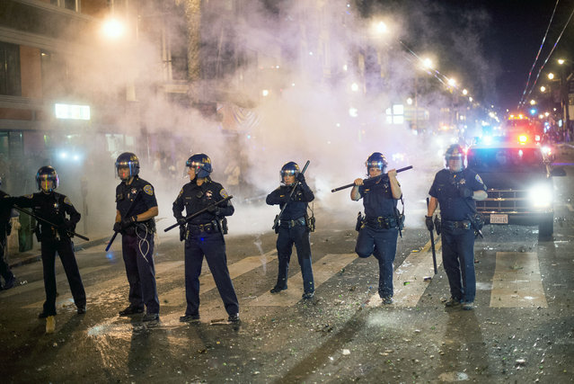 San Francisco police officers work to break up a large crowd who were celebrating after the San Francisco Giants won the World Series baseball game against the Kansas City Royals on Wednesday, October 29, 2014, in San Francisco. (Photo by Noah Berger/AP Photo)
