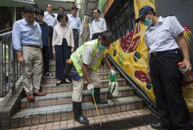 A government worker pumps anti-mosquito spray into gutters and drains as Hong Kong government officials from the Food and Environmental Health Department and the Department of Health look on, in the mid-Levels, Central District, Hong Kong, China, 08 September 2016. This year to date there have been three reported cases of the deadly mosquito-borne dengue fever in Hong Kong, and all three cases involved people living in the mid-Levels area. Hong Kong has also reported one case of the mosquito-borne Zika virus. (Photo by Alex Hofford/EPA)