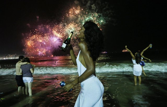 Revelers celebrate during fireworks marking the start of the New Year on Copacabana beach on January 1, 2017 in Rio de Janeiro, Brazil. (Photo by Mario Tama/Getty Images)