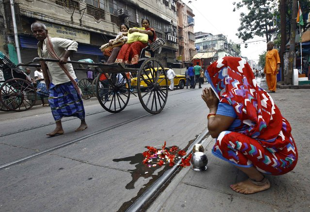 A woman offers prayers by a road as a rickshaw puller transports passengers in Kolkata October 28, 2014. (Photo by Rupak De Chowdhuri/Reuters)
