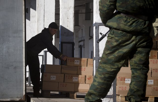 In this photo taken on Tuesday, October 28, 2014, pro-Russian rebels load boxes with canned beef in a warehouse in the town of Donetsk, eastern Ukraine. (Photo by Dmitry Lovetsky/AP Photo)