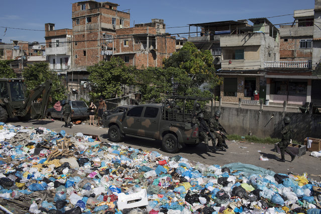 Soldiers patrol on a street littered with trash  in a surprise operation in the Jacarezinho slum in Rio de Janeiro, Brazil, Thursday, January 18, 2018. (Photo by Leo Correa/AP Photo)