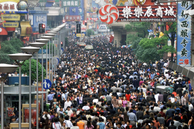 Chinese revellers flock along Shanghai's busy Nanjing Road May 1, 2002. Throngs of people flock to China's financial capital to celebrate a week-long Labor Day holiday to honor workers worldwide. (Photo by Claro Cortes IV/Reuters)