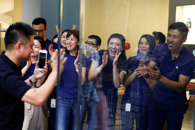 Staff members applaud a customer as he arrives to purchase Apple's new iPhone 7 at an Apple store in Beijing, China, September 16, 2016. (Photo by Thomas Peter/Reuters)