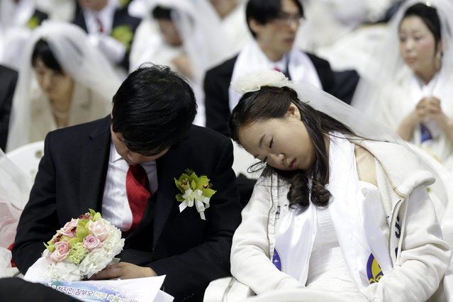 A newly-married couple takes a nap before their mass wedding ceremony at the CheongShim Peace World Center in Gapyeong, South Korea, Sunday, February 17, 2013. Some 3,500 South Korean and foreign couples exchanged or reaffirmed marriage vows in the Unification Church's mass wedding arranged by Hak Ja Han Moon, a wife of the late Rev. Sun Myung Moon, the controversial founder of the Unification Church. (Photo by Lee Jin-man/AP Photo)