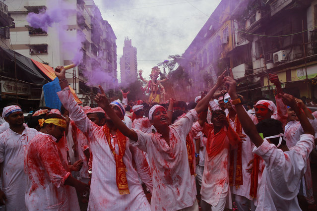 Hindu devotees participate in a procession towards the Arabian Sea where a giant idol of the elephant-headed god Ganesha will be immersed on the final day of the ten-day long Ganesha Chaturthi festival in Mumbai, India, Thursday, September 15, 2016 . The last day of the 10-day celebration is the biggest day, with massive crowds singing and dancing as they carry their idols through the streets, to immerse them in the water, an act that symbolizes sending the god back to his mythical home in the snow-capped mountains taking all the worries and problems of his worshippers with him. (Photo by Rafiq Maqbool/AP Photo)