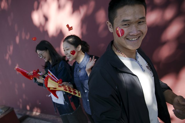 A man smiles after he placed a sticker in national colours on his face near the Tiananmen Gate as people celebrate National Day marking the 66th anniversary of the founding of the People's Republic of China in Beijing October 1, 2015. (Photo by Damir Sagolj/Reuters)