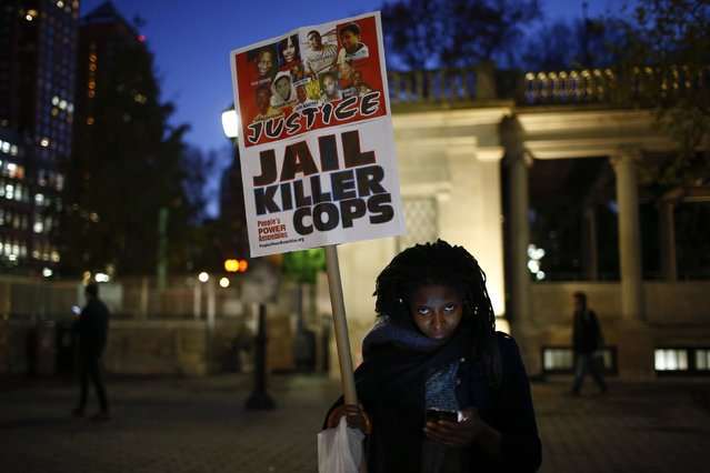 A woman holds a sign with images of Eric Garner and Michael Brown, among others, as protesters begin to rally in New York, November 24, 2014, after the grand jury reached a decision in the death of 18-year-old Brown in Ferguson, Missouri. (Photo by Eduardo Munoz/Reuters)