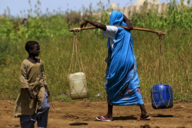A woman carries water during a visit by a European Union delegation, at an Internally Displaced Persons (IDP) camp in Azaza, east of Ad Damazin, capital of Blue Nile state, Sudan October 21, 2015. (Photo by Mohamed Nureldin Abdallah/Reuters)