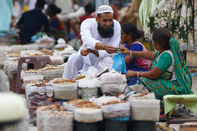 A Pakistani woman sells dry fruit on a road side after the government lifted most of the country's remaining coronavirus restrictions, in Karachi, Pakistan, 19 August 2020. (Photo by Shahzaib Akber/EPA/EFE/Rex Features/Shutterstock)