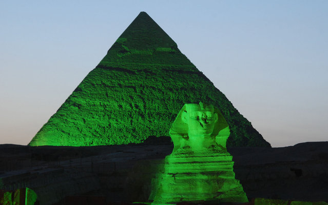 A picture shows one of the three Giza Pyramids and the Sphinx (foreground) lit in green on the occasion of St. Patrick's Day on March 15, 2013 in Giza. Egypt. (Photo by AFP Photo/Irish Embassy)