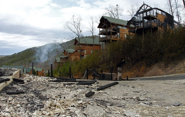 The remains of cabins at the Black Bear Ridge Resort can be seen, Monday, March 18, 2013 where a fire destroyed or damaged 65 structures and charred 165 acres between Pigeon Forge and the Wears Valley area of Sevier County, Tenn. by noon on Monday, March 18, 2013. The fire was reported on Sunday afternoon. The area in the foreground is where the fire started. (Photo by Wade Payne/AP Photo)