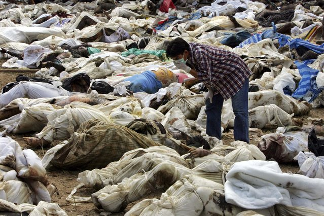 A Thai man searches for his relative amid hundreds of corpses in a temple off the coast of Ban Muan, Thailand in this December 29, 2004 file photo. (Photo by Reuters/Stringer)