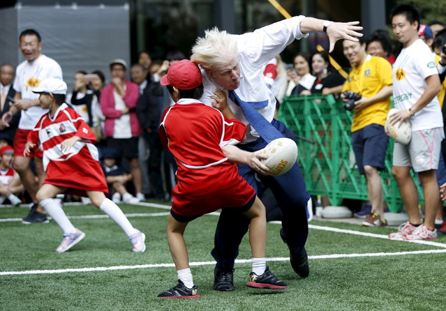 London's Mayor Boris Johnson (front R) collides with 10-year-old Toki Sekiguchi during a game of Street Rugby with a group of Tokyo children, outside the Tokyo Square Gardens building October 15, 2015. (Photo by Issei Kato/Reuters)