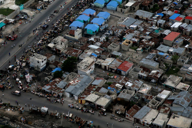 People walk down the street as Hurricane Matthew approaches in Port-au-Prince, Haiti, October 2, 2016. (Photo by Carlos Garcia Rawlins/Reuters)