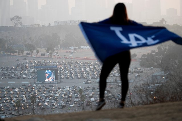 A person holds a flag while watching a drive-in viewing of Los Angeles Dodgers against the Tampa Bay Rays during game 1 of the 2020 World Series in the parking lots of Dodgers Stadium as seen from Angels Point during the outbreak of the coronavirus disease (COVID-19), in Los Angeles, California, U.S., October 20, 2020. (Photo by Mario Anzuoni/Reuters)