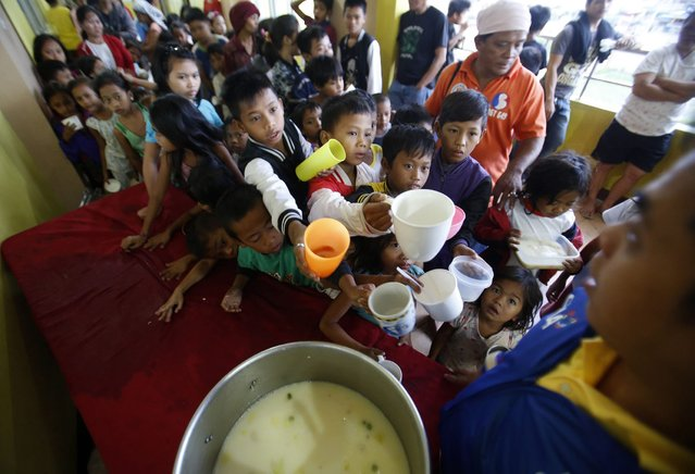 Children queue for food at an evacuation centre for the coastal community, to shelter from typhoon Hagupit, near Manila, December 8, 2014. Hundreds of thousands of Filipinos began to return to their homes battered by a powerful typhoon at the weekend, but the nation collectively breathed a sigh of relief as a massive evacuation plan appeared to minimise fatalities. (Photo by Cheryl Gagalac/Reuters)