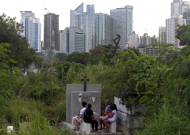 Residents visit the grave of a departed loved one inside a public cemetery in Makati financial district of Manila October 31, 2015. Filipinos flock to cemeteries across the country to commemorate their departed loved ones for All Saints and All Souls Days, which fall on November 1 and 2 respectively. (Photo by Janis Alano/Reuters)