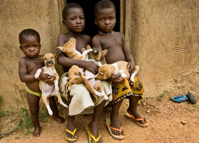 """We were traveling through Benin when an adobe building caught our eye. We stopped to photograph it and suddenly some children trailed by puppies appeared. This image captures one of many serendipitous moments we encountered in our travels"". (Photo by Art Wolfe/Art Wolfe Stock)"
