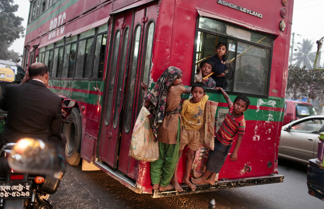 Bangladeshi street children hang onto a moving bus in Dhaka, Bangladesh, Wednesday, December 10, 2014. A 2013 World Bank report said there was a continuous decline in the number of poor people in Bangladesh, one of the most densely populated countries in the world, from nearly 63 million in 2000, to 55 million in 2005, and then 47 million in 2010. (Photo by A. M. Ahad/AP Photo)