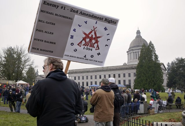A man carries a sign as gun rights advocates rally against Initiative 594 at the state capitol in Olympia, Washington December 13, 2014. (Photo by Jason Redmond/Reuters)