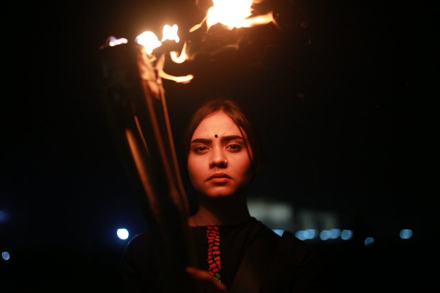 A female activist holds torch during a torch-lit protest demanding women's safety and justice for rape victims in Dhaka, Bangladesh, October 14, 2020. (Photo by Rehman Asad/Barcroft Media via Getty Images)