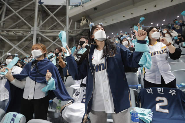 Fans wearing face masks to help protect against the spread of the coronavirus cheer during Game 1 of the Korean Series, the Korea Baseball Organization's championship round, between Doosan Bears and NC Dinos at Gocheok Sky Dome in Seoul, South Korea, Tuesday, November 17, 2020. South Korea says it will tighten social distancing rules in the greater Seoul area and some parts of eastern Gangwon province to try to suppress a coronavirus resurgence there. (Photo by Ahn Young-joon/AP Photo)