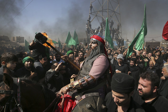 A Shiite re-enacts the events of Ashoura while Iranian and Iraqi Shiite Muslims mourn in a procession in southern Tehran, Iran, Wednesday, October 12, 2016. Shiites mark Ashoura, the tenth day of the Muslim month of Muharram, to commemorate the martyrdom of Imam Hussein, a grandson of Prophet Muhammad and one of Shiite Islam's most beloved saints, during the 7th century Battle of Karbala in present-day Iraq. (Photo by Vahid Salemi/AP Photo)