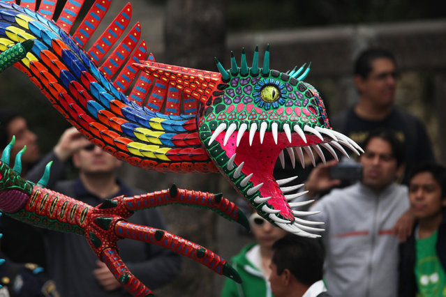 A giant alebrije is paraded through Mexico City, Saturday, December 13, 2014. (Photo by Marco Ugarte/AP Photo)