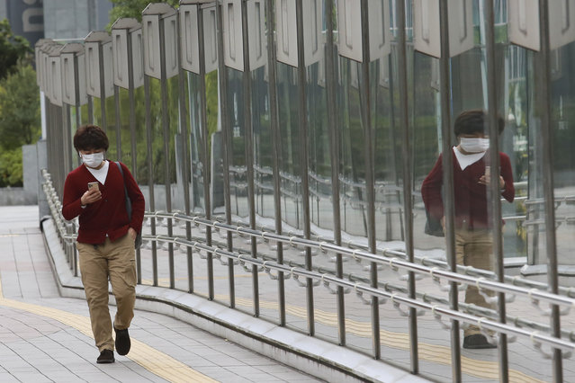 A man wearing a face mask to protect against the spread of the coronavirus walks on a pedestrian overpass in Tokyo, Tuesday, November 24, 2020. (Photo by Koji Sasahara/AP Photo)