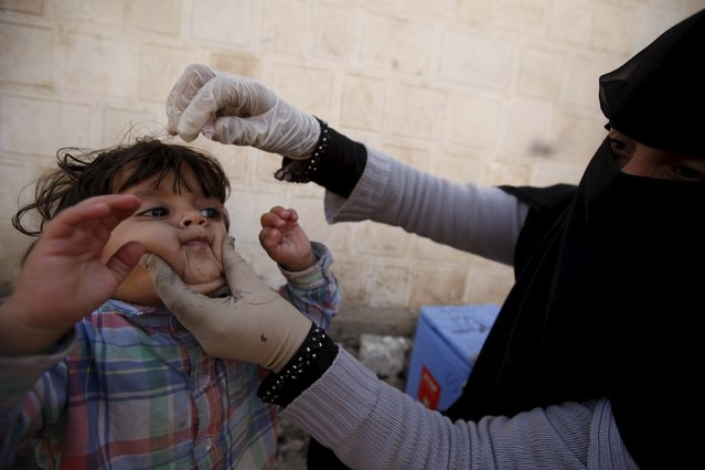 A boy reacts as he receives polio vaccine drops during a house-to-house vaccination campaign in Yemen's capital Sanaa November 10, 2015. REUTERS/Khaled Abdullah
