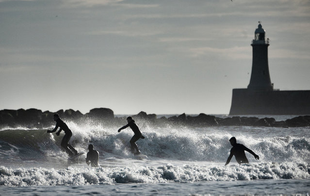 Surfers silhouetted against the waves at Tynemouth, near North Shields, England on November 12, 2020. (Photo by Owen Humphreys/PA Images via Getty Images)