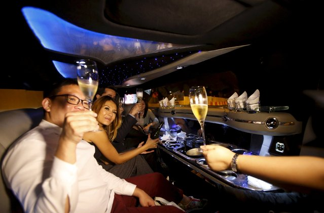 People raise their glasses as they are chauffeured in a stretch limousine, Singapore July 23, 2015. (Photo by Edgar Su/Reuters)