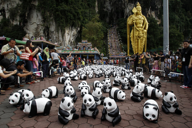 """Part of the 1,600 paper pandas, created by French artist Paulo Grangeon, are displayed in front of a giant statue of Lord Murugan during the month-long """"1600 Pandas World Tour"""" at Batu Caves in Kuala Lumpur, Malaysia, Tuesday, December 30, 2014. (Photo by Lai Seng Sin/AP Photo)"""