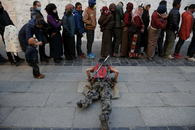 A Tibetan man prostrates himself in front of pilgrims waiting to enter the Jokhang Temple in central Lhasa, Tibet Autonomous Region, China earlyNovember 20, 2015. (Photo by Damir Sagolj/Reuters)