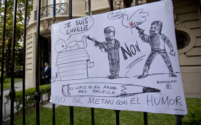 "A cartoon style drawing hangs outside France's embassy that reads in Spanish ""The pencil is the most peaceful weapon, don't mess with humor"" in solidarity with those killed in an attack at the Paris offices of the weekly newspaper Charlie Hebdo in Buenos Aires, Argentina, Wednesday, January 7, 2015. (Photo by Natacha Pisarenko/AP Photo)"