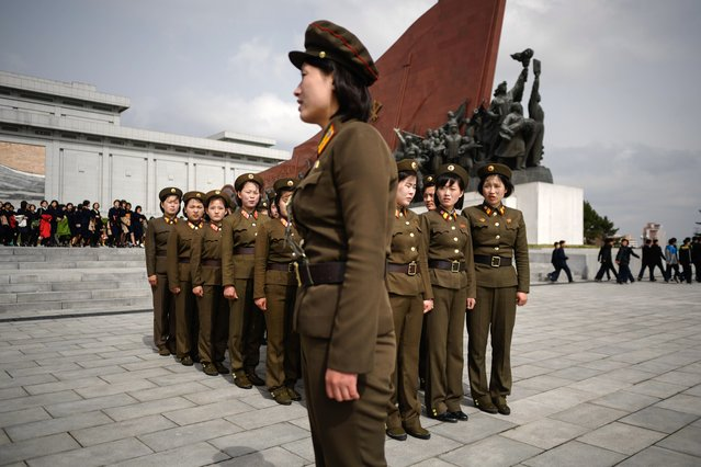 Female Korean People' s Army (KPA) soldiers gather after paying their respects before the statues of late North Korean leaders Kim Il Sung and Kim Jong Il, at Mansu hill in Pyongyang April 15, 2018. Thousands of North Korean devotees laid flowers before statues of the country' s founder Kim Il Sung on the anniversary of his birth. Current leader Kim Jong Un is the third of the dynasty to head the isolated, nuclear- armed country, where the calendar is packed with anniversaries relating to his two forefathers and their careers. (Photo by Ed Jones/AFP Photo)
