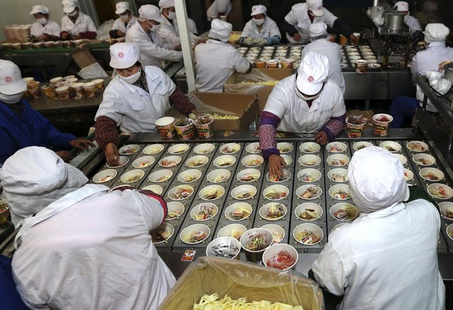 In this Sunday, January 4, 2015 photo, workers place ingredients into instant noodles packaging at a food factory in Huaibei in central China's Anhui province. China's consumer inflation edged up in December despite the slump in global oil prices but was still well below the official target. Prices rose 1.5 percent from a year earlier, up from November's 1.4 percent increase, government data showed Friday, Jan. 9. (Photo by AP Photo)
