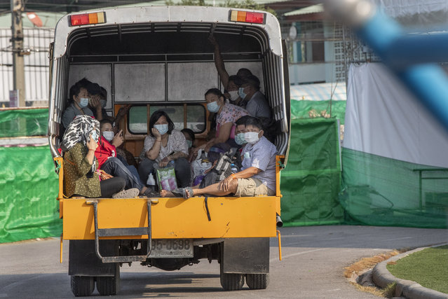 Migrant workers and their families ride in the back of a truck as they wait to be admitted to a field hospital for COVID-19 patents, Monday, January 4, 2021, in Samut Sakhon, South of Bangkok, Thailand. Thailand reported on Tuesday, Jan. 5, 2021, over 500 new coronavirus cases, most of them migrant workers who already were isolated, and the government said it was tightening movements of people around the country. (Photo by Gemunu Amarasinghe/AP Photo)