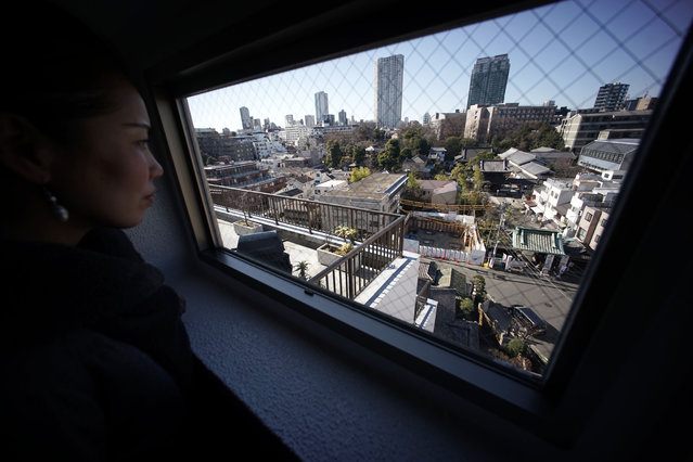 In this January 8, 2015 photo, Akane Yoshida, whose parents and grandparents run a sweet-sake shop by Sengakuji, and who leads protest against the condominium construction, watch Sengakuji temple and the condo construction site from a nearby apartment in Tokyo. (Photo by Eugene Hoshiko/AP Photo)
