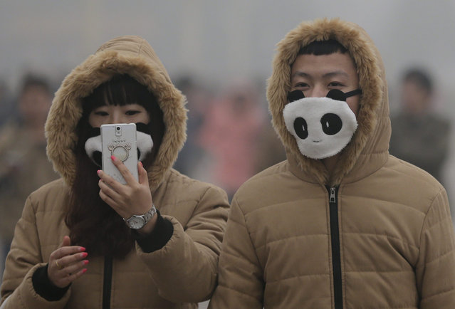 In this December 1, 2015 photo, a couple wears matching panda themed masks to protect themselves from pollutants near Tiananmen Gate on a heavily polluted day in Beijing. (Photo by Andy Wong/AP Photo)
