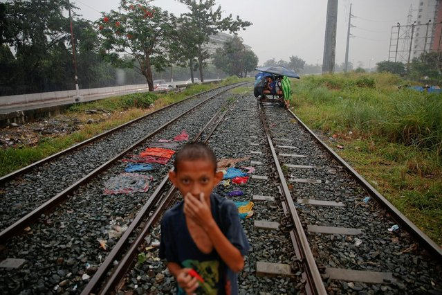A boy stands on a railroad track as a man pushes passengers on a makeshift trolley in an area where, according to local residents, several people have been killed in police operations since the beginning of country's war on drugs, in Manila, Philippines November 2, 2016. (Photo by Damir Sagolj/Reuters)