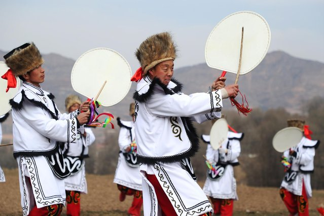 Villagers in traditional costumes perform Qiang sheep-skin drum dance in Luxi Village of Majiaji Township in Weiyuan County of Dingxi City, northwest China's Gansu Province, February 7, 2021. Qiang sheep-skin drum dance, originated from a traditional activity of the ancient Qiang ethnic group, is listed as a provincial-level intangible cultural heritage. (Photo by Xinhua News Agency/Rex Features/Shutterstock)