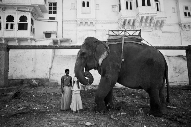 """Little Girl and the Elephant"". In front of my hotel on the river banks, Ramu the elephant and his handler came walking along and attracted this small European girl (tourist) attention. Ramu was drawn on his forehead with chalk. Location: Udaipur, India. (Photo and caption by Lauren Volo/National Geographic Traveler Photo Contest)"